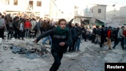 People run after what activists said was the return of government jet planes in Aleppo's al-Marja district December 23, 2013. More than 300 people have been killed in a week of air raids on the northern Syrian city of Aleppo and nearby towns by President
