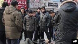 一名外國記者在星期日採訪茉莉花示威時被推倒地上﹐旁邊被多名不明身份的人圍著