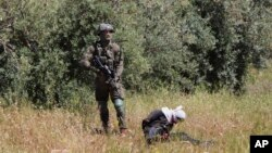 An Israeli soldier stands over handcuffed and blindfolded Osama Hajahjeh, 16, after he was shot near the village of Tekoa, West Bank, Apri 18, 2019.