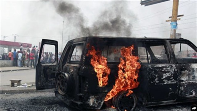 Local residents look on as a UN vehicle, set on fire by militant student supporters of Laurent Gbagbo, burns in the Riviera 2 neighborhood of Abidjan, 13 Jan 2011