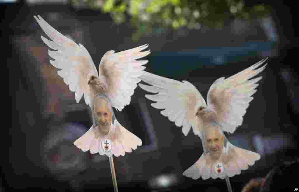 Fiéis acenam com pombas brancas com fotos do papa Francisco na cidade do México.