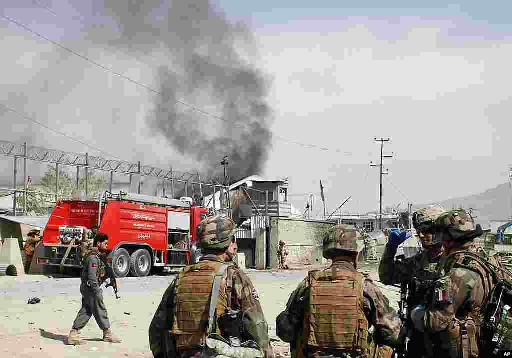 Tentara NATO bercakap-cakap satu sama lain di depan asap yang mengepul dari ledakan bom mobil di Kabul (AP).