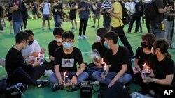 រូបឯកសារ៖ សកម្មជនហុងកុងលោក Joshua Wong (កណ្តាល) និងសកម្មជនគាំទ្រលទ្ធិប្រជាធិបតេយ្យផ្សេងទៀត ក្នុងអំឡុងពេលប្រមូលផ្តុំគ្នារំឭកដល់ការបង្ក្រាបបាតុករ ឆ្នាំ ១៩៨៩ នៅទីលាន Tiananmen នៅសួន Victoria ក្រុងហុងកុង កាលពីថ្ងៃទី ៤ ខែមិថុនា ឆ្នាំ ២០២០។