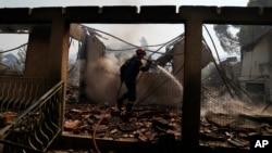 Seorang petugas pemadam kebakaran menjatuhkan air di sebuah rumah yang terbakar akibat kebakaran hutan di daerah Vilia sekitar 60 kilometer barat laut Athena, Yunani, Senin, 23 Agustus 2021. (AP Photo/Thanassis Stavrakis)