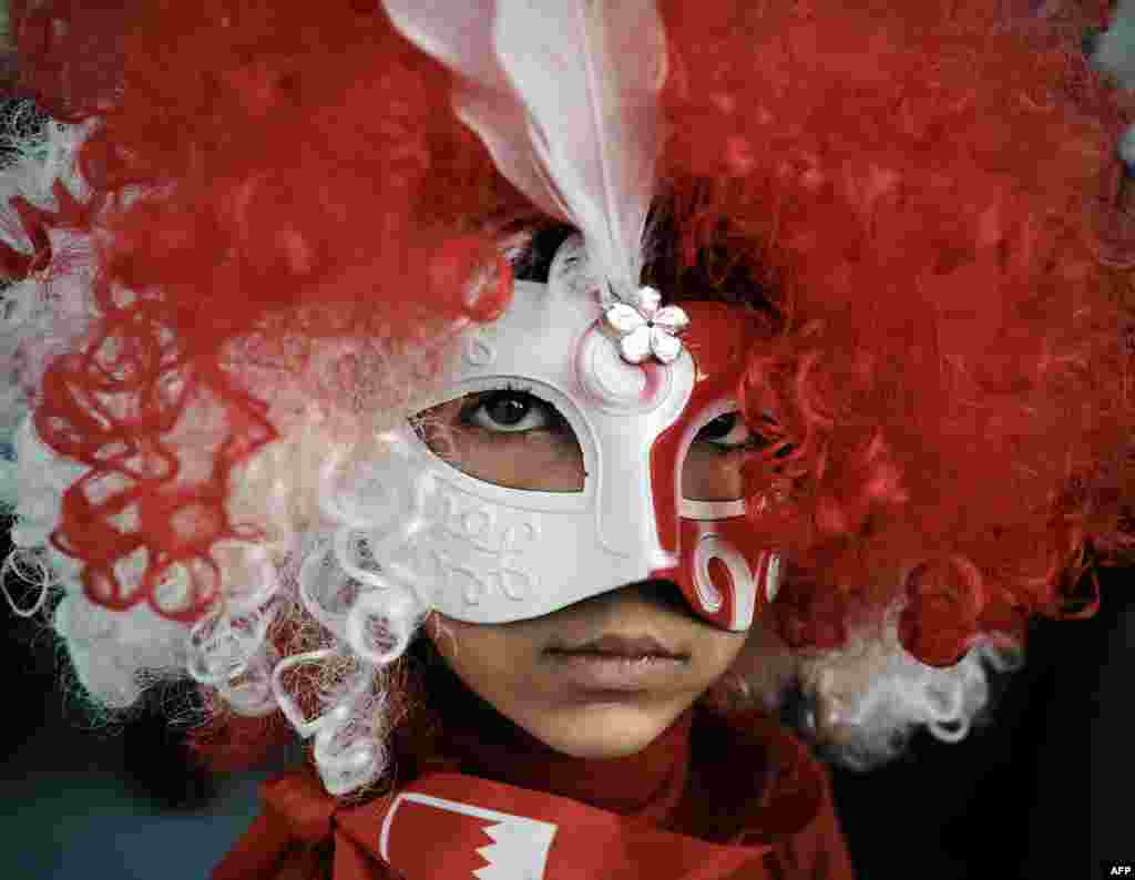 A young Bahraini girl wearing a mask poses during an anti-government protest in the village of Shakhora, west of Manama.