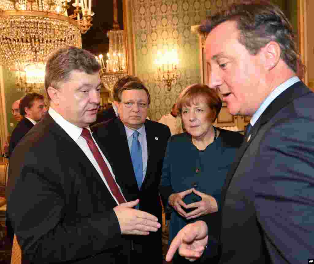 From left, Ukraine's President Petro Poroshenko, EU Commission President Jose Manuel Barroso, German Chancellor Angela Merkel and British Prime Minister David Cameron meet on the sidelines of the ASEM summit of European and Asian leaders in Milan, Oct. 17, 2014.