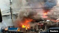 Houses are engulfed in fire after a bomb attack in the centre of Cotabato city in southern Philippines, Aug. 5, 2013.