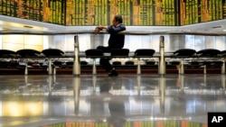 一个访客坐在马来西亚吉隆坡一个私人股票交易所的交易牌前。