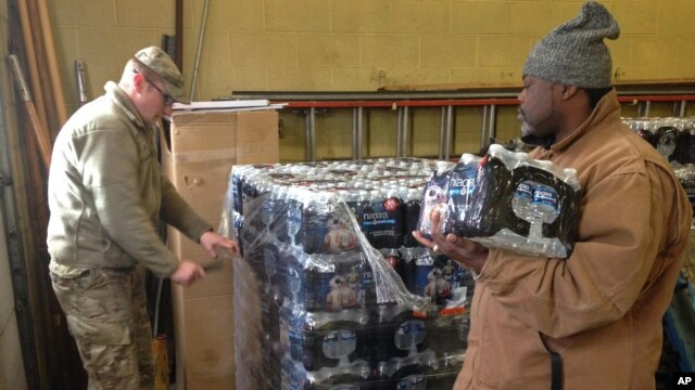 Staff Sgt. William Phillips, with the Michigan National Guard, assists a resident at a water distribution center Wednesday, Jan. 13, 2016, at a fire station in Flint, Michigan.