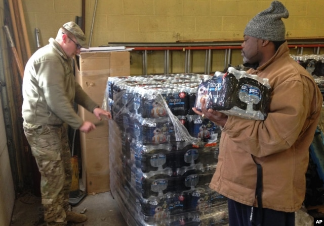 FILE - Staff Sgt. William Phillips, with the Michigan National Guard, assists a resident at a water distribution center at a fire station in Flint, Mich., Jan. 13, 2016.