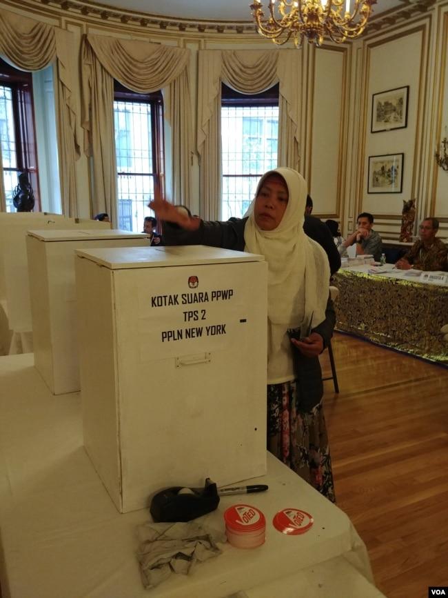WNI memasukkan surat suara ke kotak dalam pemilu serentak di KJRI New York, Sabtu 13/4 (VOA/Naratama).