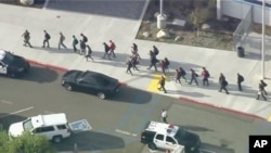 People are lead out of Saugus High School after reports of a shooting on Thursday, Nov. 14, 2019 in Santa Clarita, Calif. (KTTV-TV via AP)
