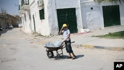 A Libyan boy carries water in a wheel barrow in Tripoli. Water has been cut off throughout the city, August 26, 2011