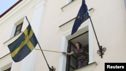 An employee rearranges the national flag of Sweden at the Swedish embassy in Minsk August 8, 2012