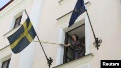Работница шведского посольства сворачивает флаг. Минск, Беларусь