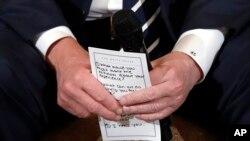 Presiden AS Donald Trump memegang catatan saat mendengarkan pandangan dari para siswa dan guru SMU Marjory Stoneman Douglas High School di Parkland, Florida, di Gedung Putih hari Selasa (21/2).