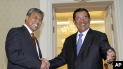 Malaysia's Defense Minister Ahmad Zahid Hamidi (L) shakes hands with Cambodia's Prime Minister Hun Sen during meeting at the Office of the Council of Ministers in Phnom Penh July 28, 2011.