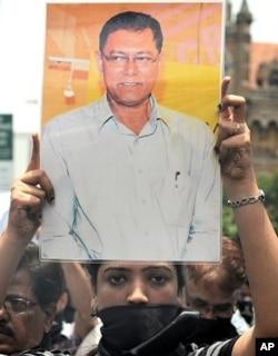 ممبئی میں مظاہرین مقتول بھارتی صحافی جیوترمائے ڈے کی تصویر اٹھائے ہوئے۔13 جون، 2011