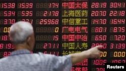 Một nhà đầu tư đang nhìn vào bảng điện tử tại một trung tâm giao dịch ở Thượng Hải, Trung Quốc, ngày 30/6/2015.