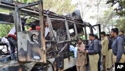 15일 폭탄 테러를 당한 한 파키스탄의 한 여자대학교 통학버스 현장에서 당국 관계자들이 조사를 벌이고 있다.