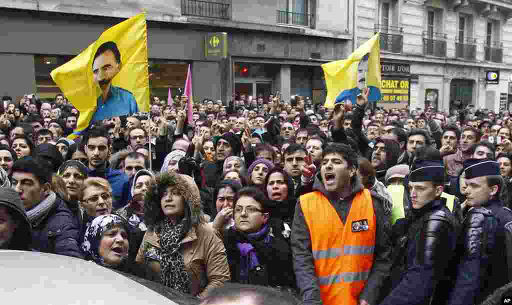 Kurdish people react as three bodies of the killed Kurdish women are taken out of a building in Paris, France, January 10, 2013.