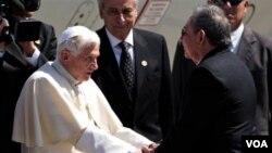 Paus Benediktus XVI disambut Presiden Kuba, Raul Castro di bandara kota Santiago hari Senin (26/3).