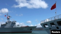 China's replenishment ship, Qiandaohu, left, sails past its hospital ship, Peace Ark, as it docks in Honolulu, Hawaii.