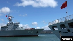 FILE - China's replenishment ship, Qiandaohu, left, sails past its hospital ship, Peace Ark, as it docks in Honolulu, Hawaii.
