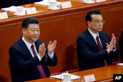 FILE - Chinese President Xi Jinping, left, and Chinese Premier Li Keqiang applaud during the opening session of the annual National People's Congress at the Great Hall of the People in Beijing, March 5, 2018.