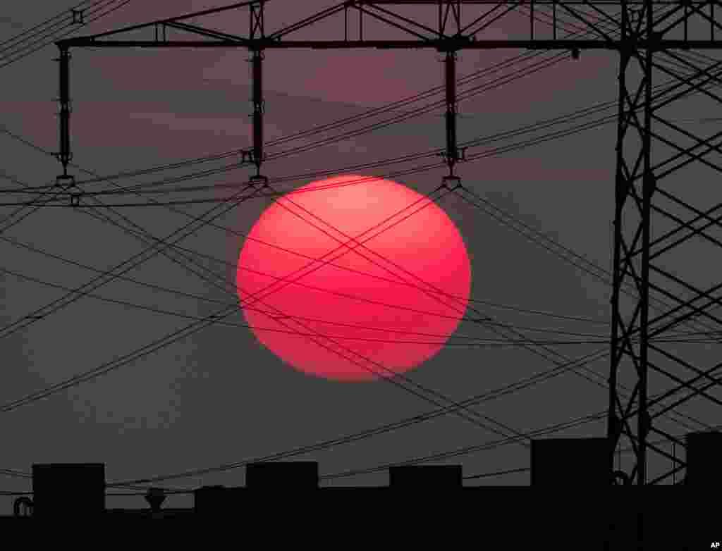 عکسی از طلوع آفتاب در پس خطوط فشار قوی برق در حاشیه شهر فرانکفورت، آلمان.
