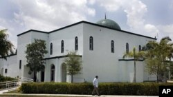 A pedestrian walks past the Jamat Al-Mummineen Mosque in Margate, Florida, where imam Izhar Khan has been charged with providing financial support to the Pakistani Taliban, May 14, 2011