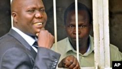 Thomas Kwoyelo (R), a former director of field operations in the rebel group Lord's Resistance Army, talks to his lawyer, Caleb Alaka, after the court ordered he should be released, in Kampala, Uganda, November 2011. (file photo)