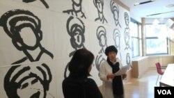 주한독일대사관에서 열리고 있는 '슬픔의 벽' 전시회에서 김혜련 작가(오른쪽)가 북한 병사를 그린 작품 '너의 얼굴' 앞에서 작품 설명을 하고 있다.