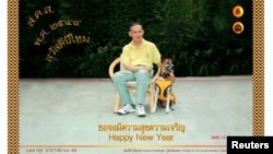 FILE - Thailand's King Bhumibol Adulyadej poses with his favorite dog, Khun Thongdaeng, in a New Year's greeting card addressed to the Thai people, Dec. 7, 2005.