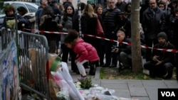 A girl lays flowers as part of a memorial to victims of the terror attacks in Paris, France, Nov. 14, 2015.