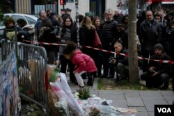 A small girl lays flowers as part of a memorial to victims a day after more than 120 people were killed in a series of attacks in Paris, Nov. 14, 2015.