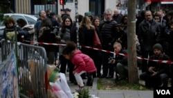 Una niña deja un ramo de flores en honor de las víctimas de los ataques de París.