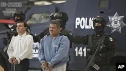 Eduardo Ramirez Valencia, alias 'El Profe,' center, and Ruben Barragan Monterrubi, alias 'El Montes,' are presented to the press at federal police headquarters in Mexico City, 02 Dec 2010