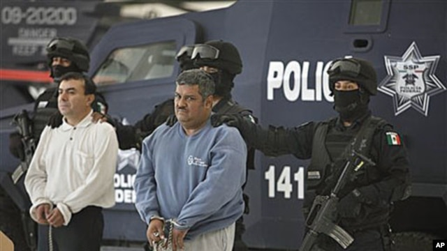 Eduardo Ramirez Valencia, alias 'El Profe,' center, and Ruben Barragan Monterrubi, alias 'El Montes,' are presented to the press at federal police headquarters in Mexico City, 02 Dec 2010