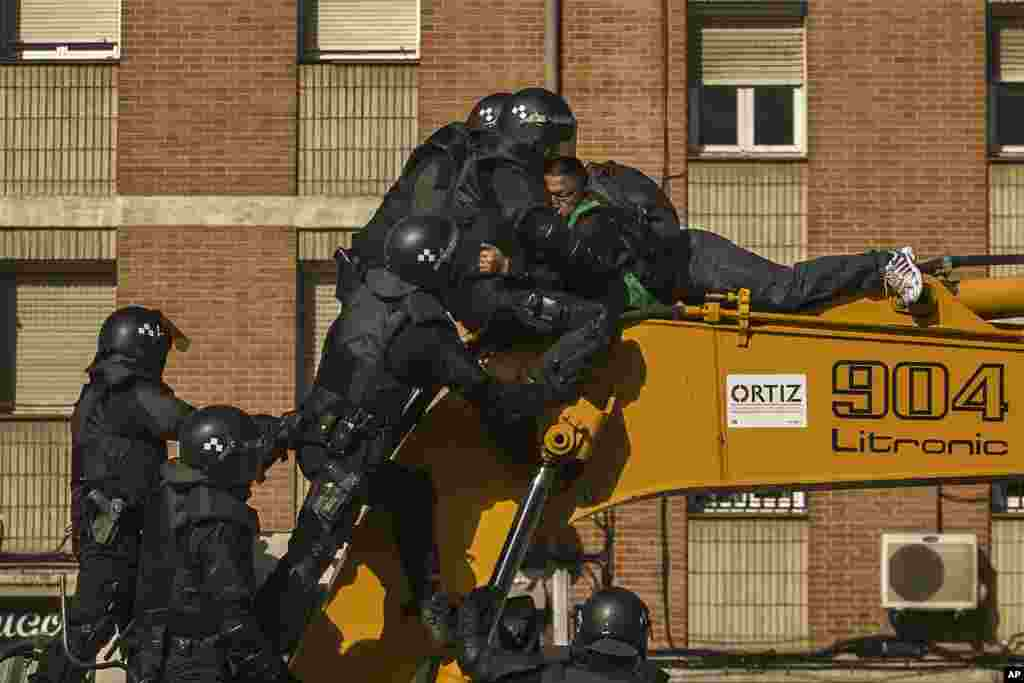 Riot Police remove a housing rights activist who climbed a bulldozer in an effort to stop the eviction of Luisa Gracia Gonzalez and her family and the demolition of their house in Madrid, Spain.