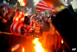 Iranian demonstrators burn representations of the U.S. flag during a protest in front of the former U.S. Embassy in response to President Donald Trump's decision Tuesday to pull out of the nuclear deal and reimpose sanctions, in Tehran, Iran, May 9, 2018.
