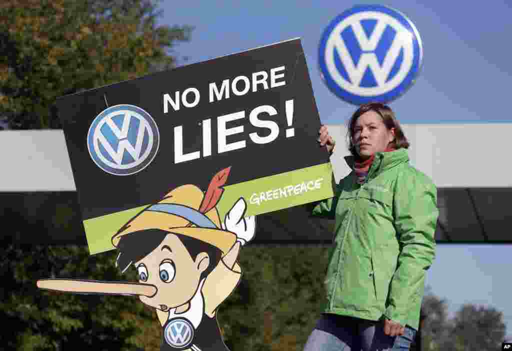 An activist of the environmental protection organization 'Greenpeace' holds a protest poster in front of a factory gate of the German car manufacturer Volkswagen in Wolfsburg, Germany. The supervisory board was meeting to discuss who to name as CEO after Martin Winterkorn quit over an emissions-rigging scandal that's rocking the world's top-selling automaker.