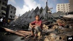 Seorang anak Palestina duduk di antara reruntuhan gedung apartemen di Gaza yang hancur akibat serangan Israel Selasa pagi (26/8).