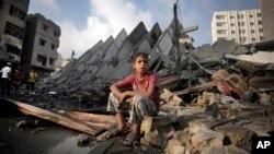 Bé trai Palestine ngồi trên đống đổ nát của tòa nhà 15 tần bị phá hủy sau các vụ không kích của Israel, ngày 26/8/2014.