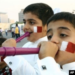 Qatari boys with their faces painted in the colors of their national flag, blow vuvuzelas, celebrating the emirate's selection as the host for the 2022 World Cup, Doha, Dec. 2, 2010.