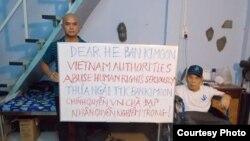 Cựu tù nhân lương tâm Phạm Bá Hải cầm biểu ngữ 'Việt Nam chà đạp nhân quyền' chào đón ông Ban Ki-moon