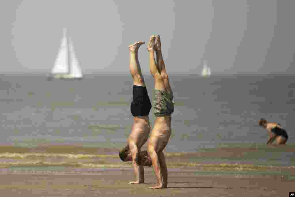 این دو مرد در ساحلی در شمال غربی بلژیک در کنار ساحل روی دست های شان ایستاده اند. موج گرما به بلژیک هم رسیده است.