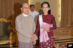 FILE - In this image provided by the Myanmar Ministry of Information, President Thein Sein, left, shakes hands with opposition leader Aung San Suu Kyi during their meeting at the presidential in Naypyitaw, Dec. 2, 2015.