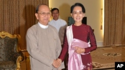 In this image provided by the Myanmar Ministry of Information, Myanmar President Thein Sein, left, shakes hands with opposition leader Aung San Suu Kyi during their meeting at the presidential in Naypyidaw, Myanmar, Dec. 2, 2015.