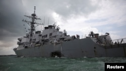 FILE - The U.S. Navy guided-missile destroyer USS John S. McCain is seen after a collision in Singapore waters, Aug. 21, 2017.